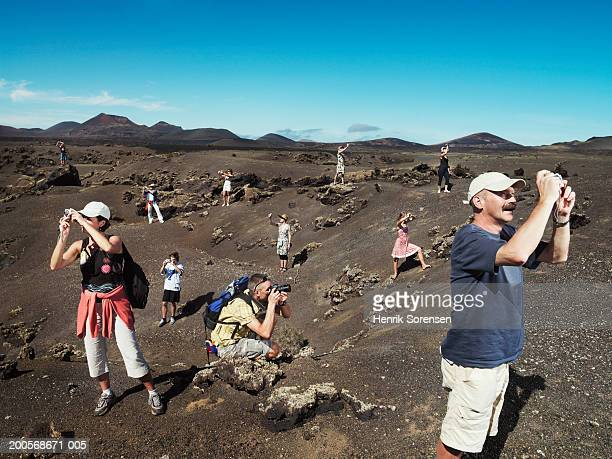 Group of tourists taking photographs in desert