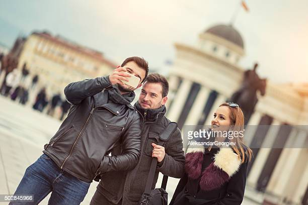 group of tourists taking photos with smartphone at city street - skopje stock pictures, royalty-free photos & images