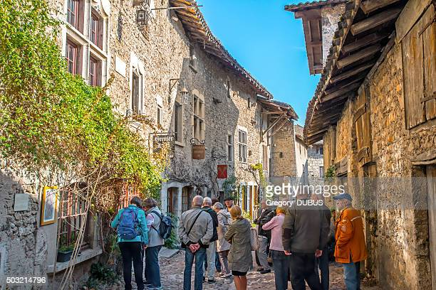 Group of tourists visiting old french medieval village of Perouges
