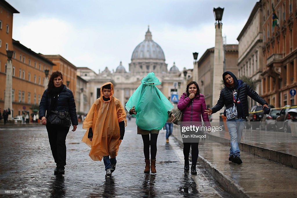 A group of tourists walk down the Via della Conciliazioneon near the Vatican in pouring rain and high winds on March 30, 2013 in Rome, Italy. Pope Francis will attend Easter mass and the 'Urbi et Orbi' blessing in St. Peter's Square tomorrow.