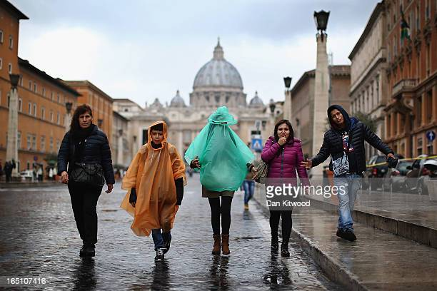 A group of tourists walk down the Via della Conciliazioneon near the Vatican in pouring rain and high winds on March 30 2013 in Rome Italy Pope...