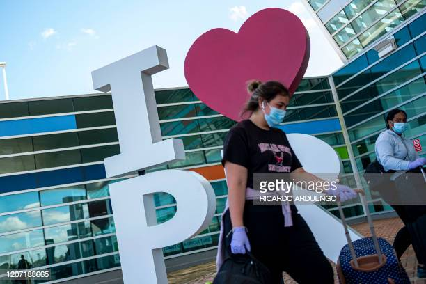 A group of tourists walk pass by a I love Puerto Rico sculpture at the Luis Munoz Marin international airport in San Juan Puerto Rico on March 14 2020