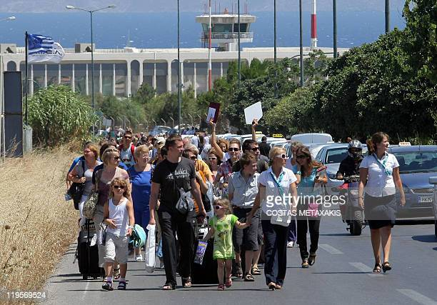 A group of tourists walks from the airport blockaded by taxi drivers owners to the Cretan capital Heraklion on July 21 2011 Hundreds of travellers...