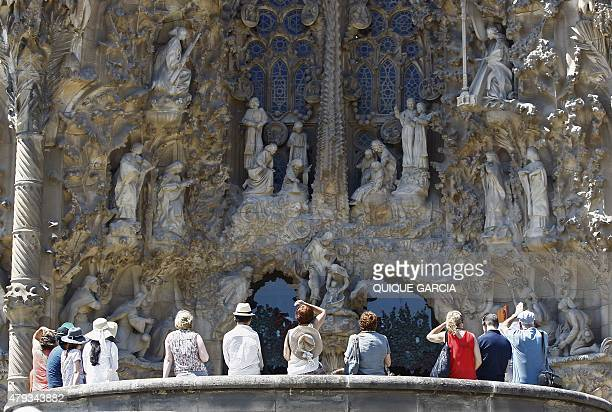A group of tourists watch the facade of Spanish architect Gaudi's Sagrada Familia basilica in Barcelona on June 28 2015 Tourists generated 14% of...