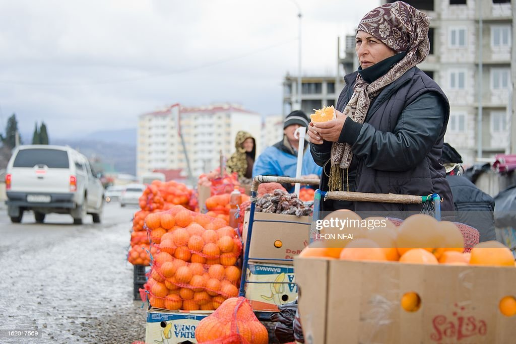 A group of traders sell oranges from the roadside in the Sochi district of Adler, on February 18, 2013. With a year to go until the Sochi 2014 Winter Games, construction work and development continues as Olympic tests events and World Championship competitions are underway.