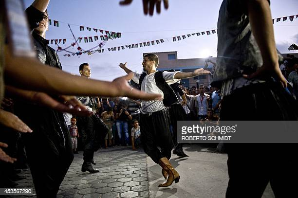 A group of traditional dancers performs during a wedding ceremony at a UN school school in Gaza City's Shati refugee camp on August 13 2014 War...