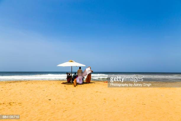 A group of traditional Kerala people with lungi under an umbrella on a sunny day at Varkala Beach, Kerala, India