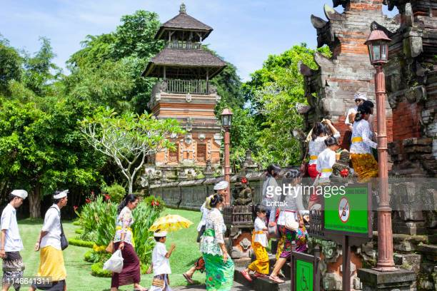 group of traditionally dressed balinese people walking up temple stairs - balinese culture stock pictures, royalty-free photos & images