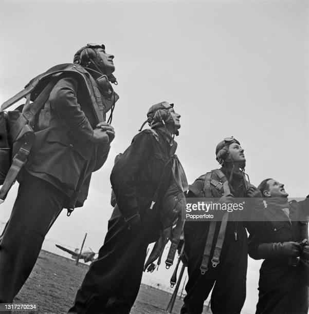 Group of trainee Royal Air Force pupil instructor pilots watch one of their colleagues in the air at a RAF School for Instructors in the United...