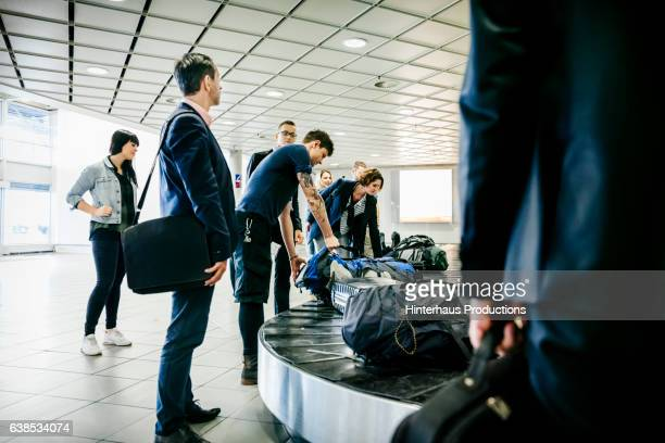 group of travellers waiting for their luggage at baggage claim - baggage claim stock pictures, royalty-free photos & images