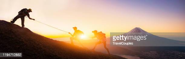 group of travellers with backpacks over sunrise background. young asian three hikers climbing up on the peak of mountain near mountain fuji. people helping each other hike up. giving a helping hand. helps and team work concept - コンセプト  ストックフォトと画像