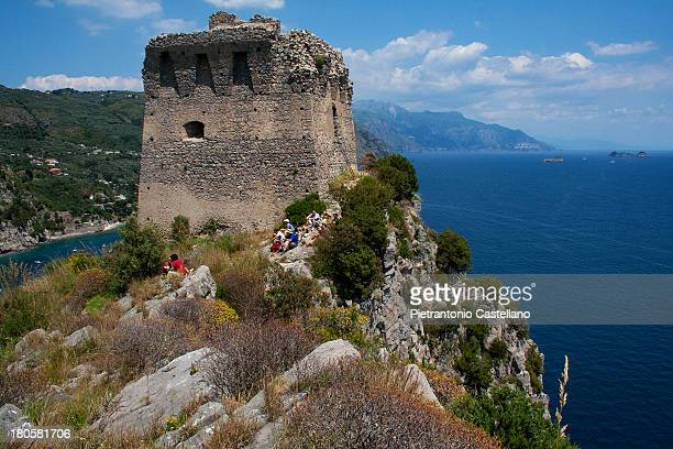 """Group of trekkers rest by the """"Torre delle Mortelle"""" Tower of Myrtle, in Massa Lubrense, on Amalfi Coast. The tower was built by the Spanish after in..."""