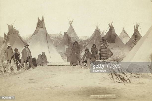 Group of twelve Miniconjou many are looking away from camerain a tepee camp probably on or near Pine Ridge Reservation