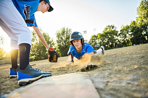 Group of two baseball players play together on the playground. On of them slide on the goal 1176575879