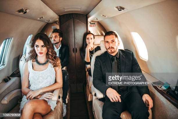 a group of two famous couples sitting side by side while traveling aboard a private airplane - side by side stock pictures, royalty-free photos & images