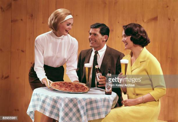 A group of two women and a man enjoy a pizza and some Ballantine beer ca 1950s United States