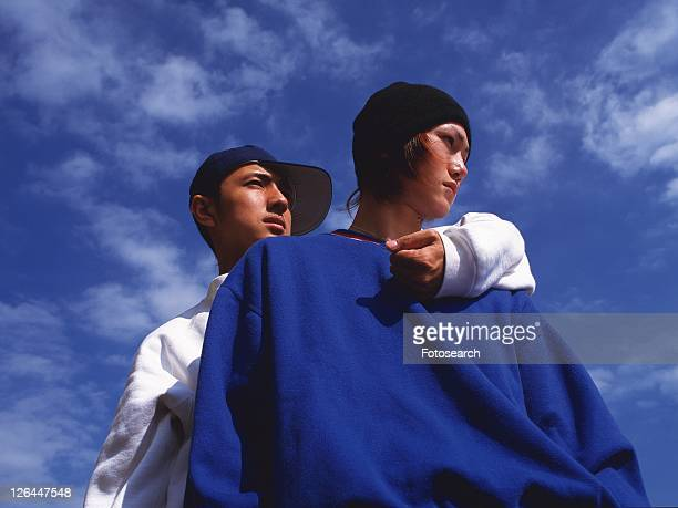 group of two young adult men posing, outdoors - low angle view photos et images de collection