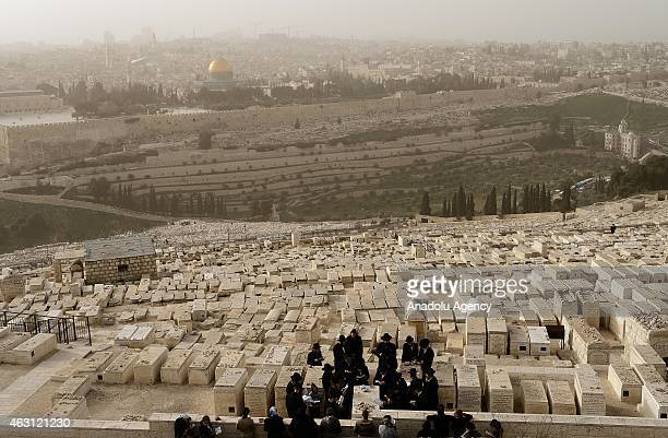 A group of Ultraorthodox Jewish men pray for their deceased relatives at the Jewish cemetery on the Mount of Olives accepted as holy by Jewish people...