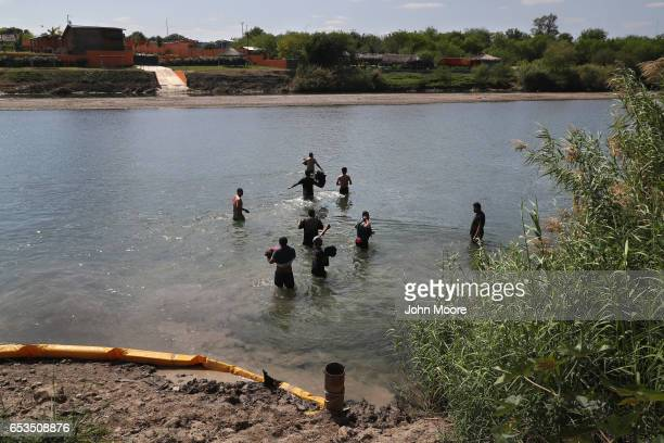 A group of undocumented immigrants wade across the Rio Grande at the USMexico border on March 14 2017 in Roma Texas US Border Patrol agents had...