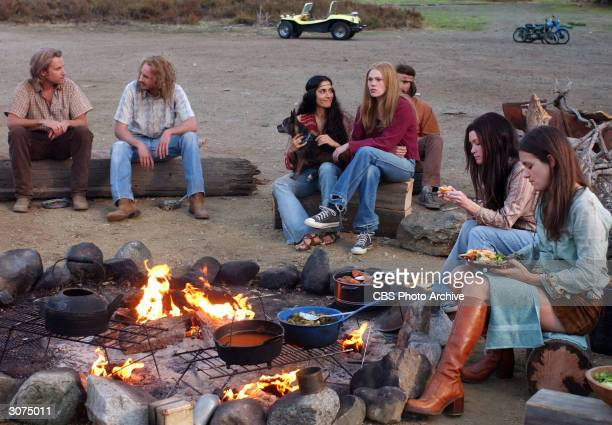 A group of unidentified actors who portray members of Charles Manson's 'family' sit and talk around a cooking fire while they eat a meal in a scene...