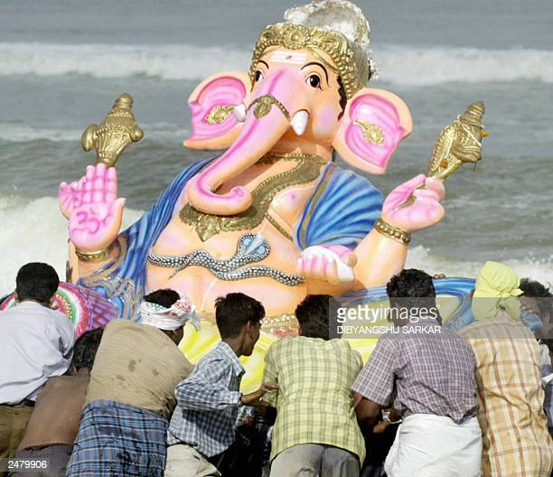 A group of unidentified Indian Hindus push an idol of the Hindu god Lord Ganesh into the sea in Madras 07 September 2003 an act which signifies the...