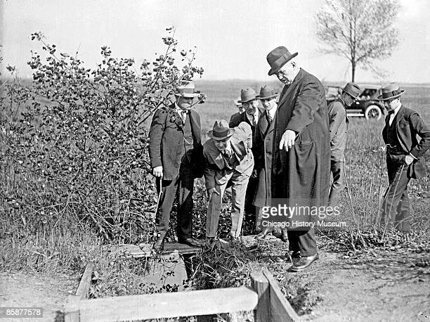 A group of unidentified men standing outdoors at the Leopold and Loeb crime scene durnig the investigation of the Bobby Franks murder case One of the...