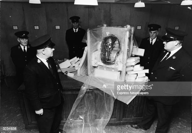A group of uniformed guards stand around the gold death mask of Egyptian King Tutankhamen on display at the British Museum London England January 31...