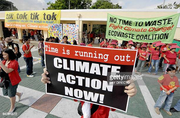 A group of university students and environmental activists rally with placards and banners in support of action against global warming during a...