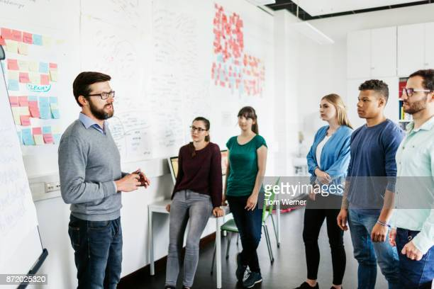 group of university students listening to tutor during seminar - college professor stock photos and pictures
