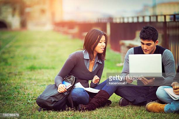 Group of university students using laptop outdoors