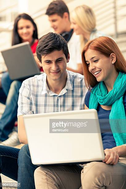 Gruppe von Studenten, die mit Laptop im Freien