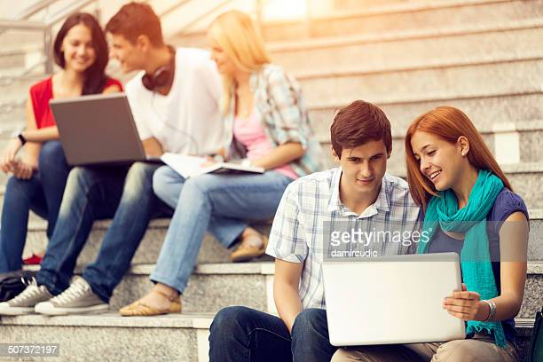Group of university students using laptops outdoors