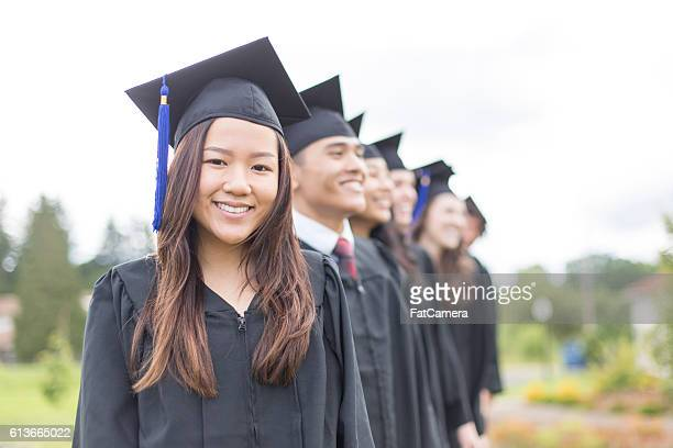 group of university students wearing graduation gowns - graduation clothing stock pictures, royalty-free photos & images