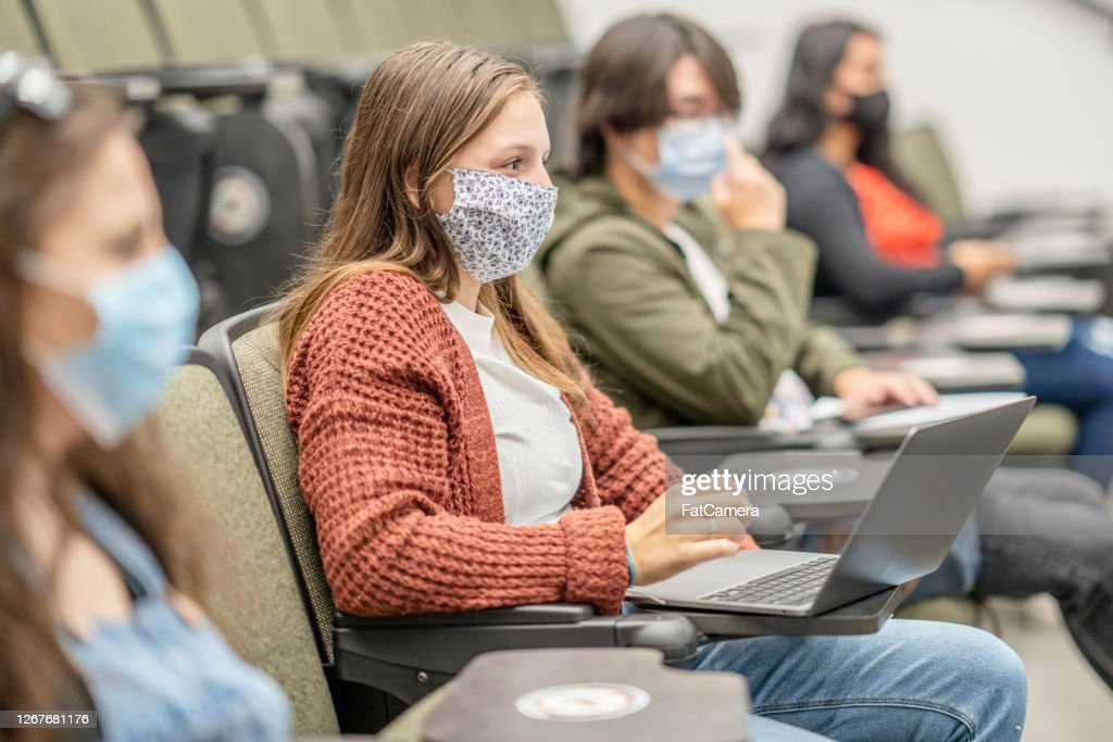 Group of university students wearing masks in class : Stock Photo