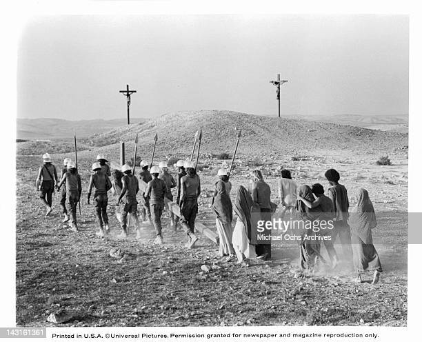 Group of unknown actors walking in line toward two men nailed to a cross on a hill in a scene from the film 'Jesus Christ Superstar', 1973.