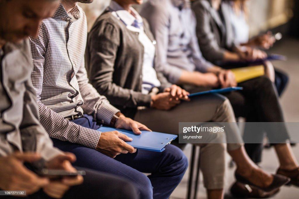 Grupo de candidatos irreconocibles a la espera de una entrevista de trabajo. : Foto de stock