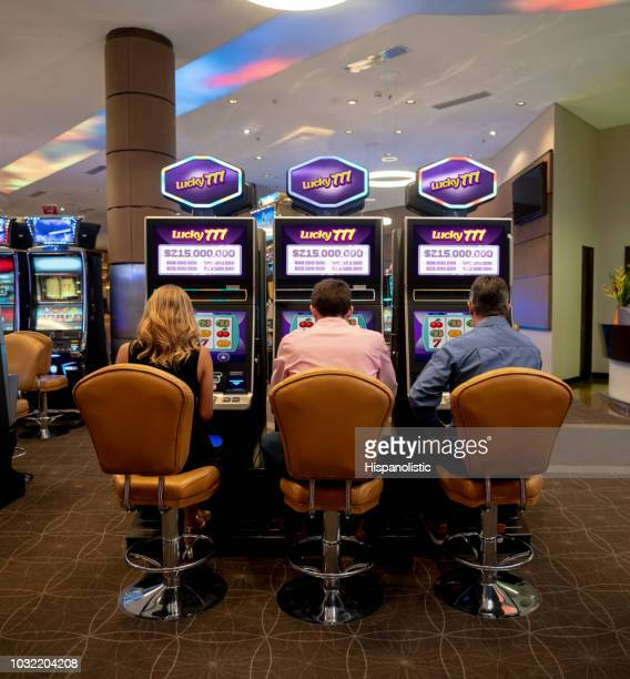 group of unrecognizable people playing on slot machines at the casino - coin operated stock photos and pictures