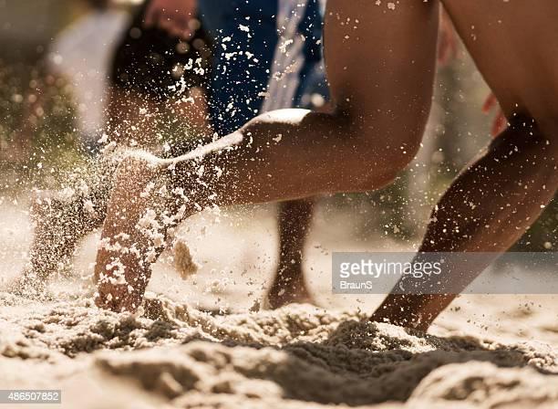 Groupe de personnes non reconnaissables courir sur la plage.