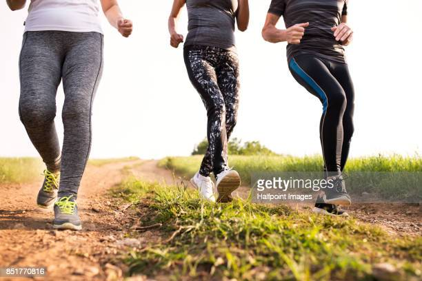 Group of unrecognizable seniors running in nature on dirt road.
