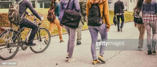 Groep onherkenbaar leerlingen wandelen door het park