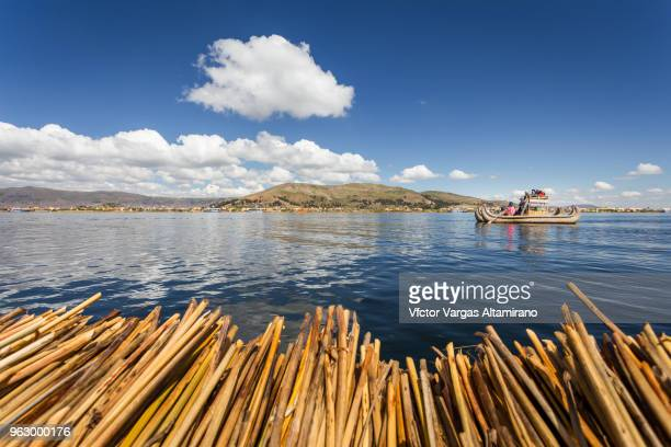 A group of Uros indigenous people and tourist in a boat navigating over the Titicaca Lake in Puno, Peru.