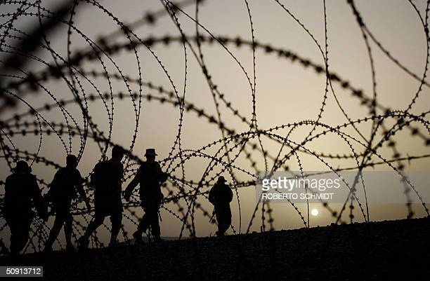 A group of US Army soldiers from the 1st Cavalry Division walks past concertina wire in the late afternoon at camp Black Jack near Baghdad 31 May...
