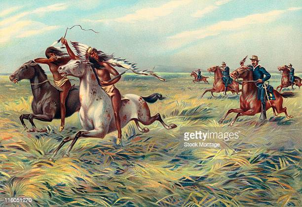 A group of US Army troops on horseback is shown in pursuit of native Americans in the American West The original caption reads 'US Army cavalry...