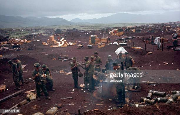 A group of US Marines eat and drink around an improvised table at Khe Sanh Vietnam