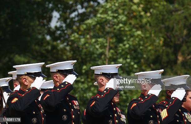 A group of US Marines salute during a full honor burial service for US Marine Cpl Kyle R Schneider at Arlington National Cemetery on July 19 2011 in...