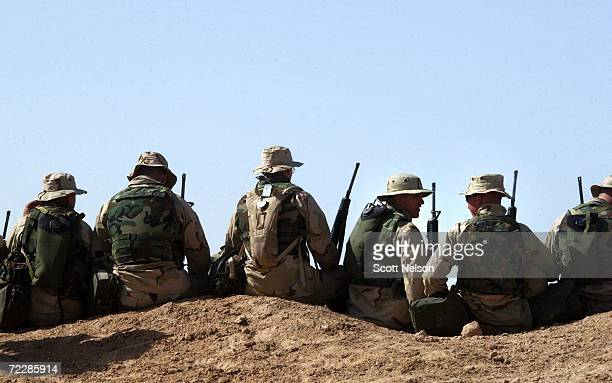 A group of US Marines take seats along the top of a dirt hill to listen to an address by Commandant of the US Marine Corps General Michael Hagee at a...