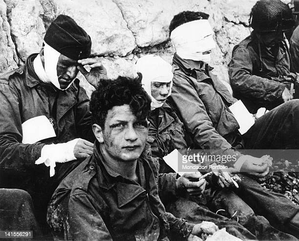 A group of US wounded soldiers sheltering behind a wall after the Normandy landing on the beach called Omaha Beach in code Normandy 6 June 1944