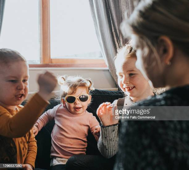 group of various aged siblings play rock, paper, scissors in a domestic environment. - humor stock pictures, royalty-free photos & images