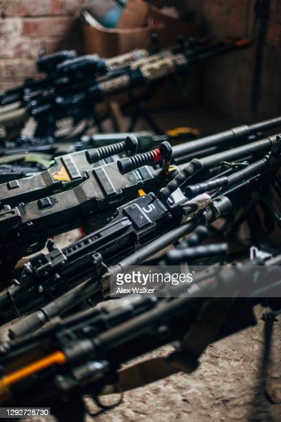 a group of various light machine guns and assault rifles resting on the floor at a forward operating base. - gunman stock pictures, royalty-free photos & images