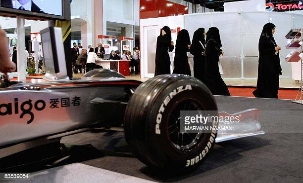 A group of veiled Emarati women walk past a Formula One simulator based on the MercedesVodaphine car of British World Champion Lewis Hamilton at the...